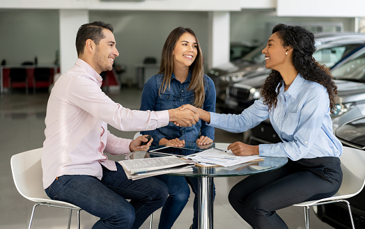 Young couple closing deal with a car saleswoman.